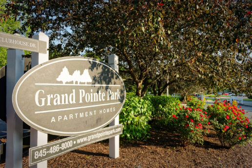 Grand Pointe Park sign with trees and foliage