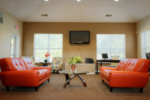 Lounge area with seating, table, and TV mounted on wall