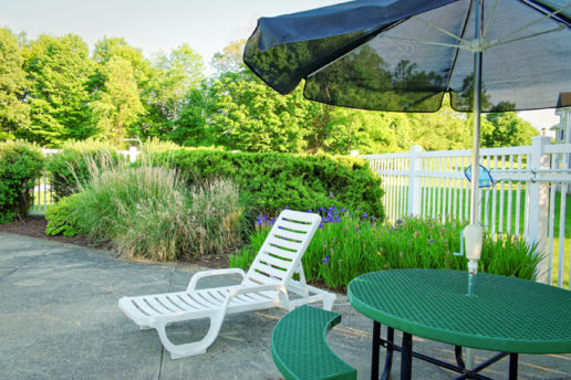 Sun chair with patio table and umbrella, foliage in background