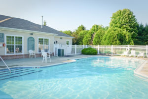 Fenced in pool with seating, sun chairs and pool house
